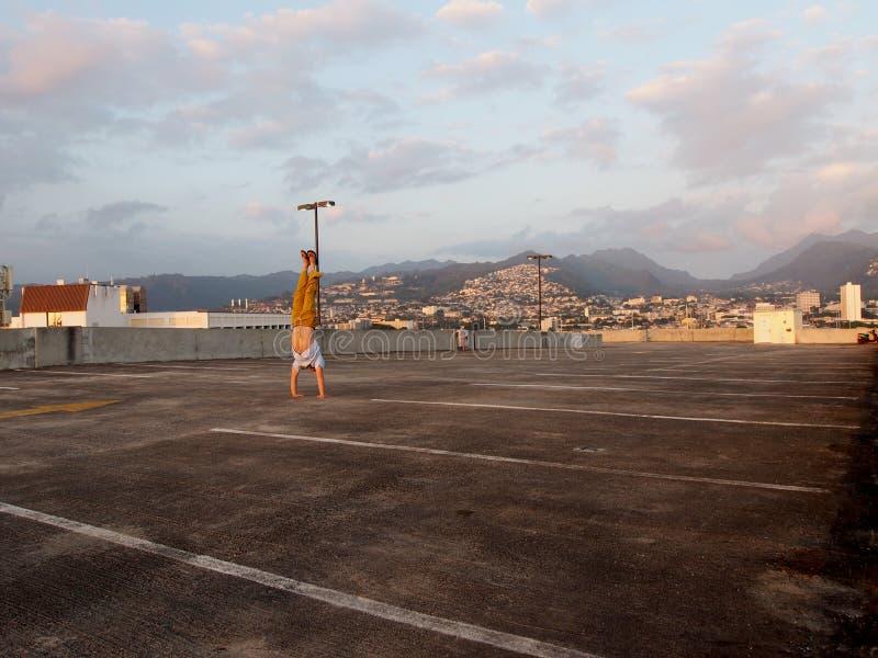 De mens doet Handstand op hoogste vloer van parkerengarage met Stad van H stock fotografie