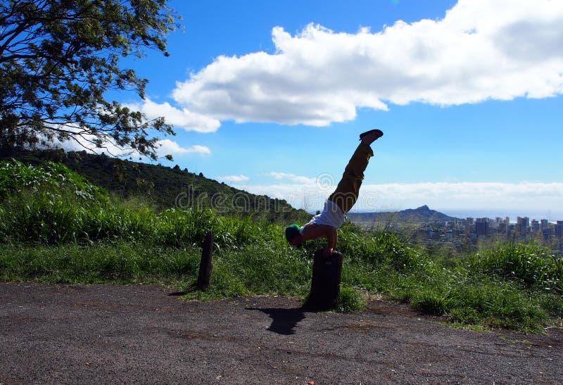 De mens doet Mayurasana of de Pauw stelt op boomstomp in mountai stock fotografie