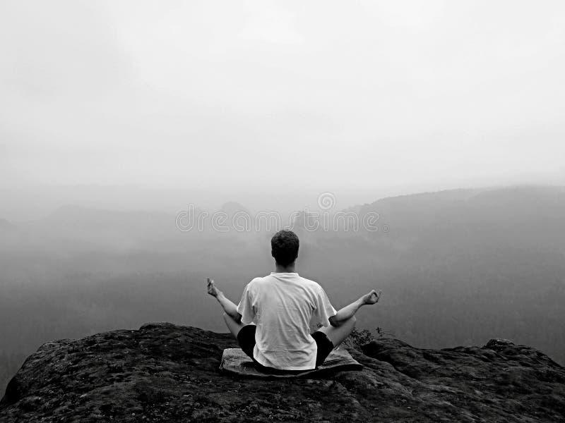 De mens doet Yoga stelt op de rotsen piek binnen nevelige ochtend stock foto's