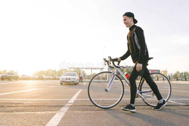 De mens in donkere sportkleding en GLB, trekt een fiets op de straat op de achtergrond van de zonsondergang en glimlacht stock afbeelding