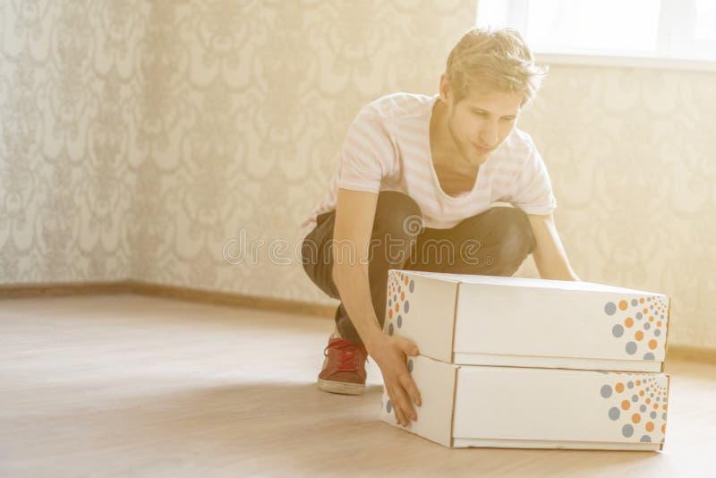 De mens draagt beeldverhaaldozen en beweegt zich aan het nieuwe huis vlakke concept F royalty-vrije stock afbeeldingen