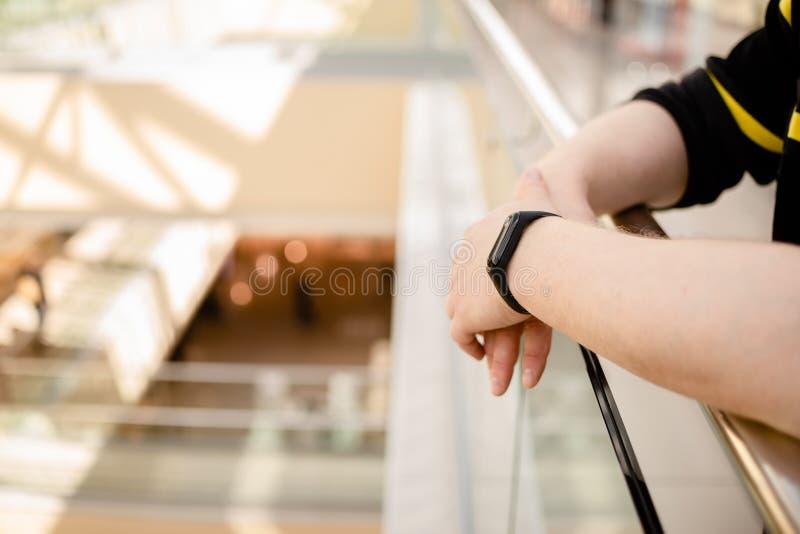 De mens draagt een geschiktheidsarmband Slim horloge op de hand van een mens Gepensioneerde die Geschiktheidsdrijver met behulp v stock afbeelding