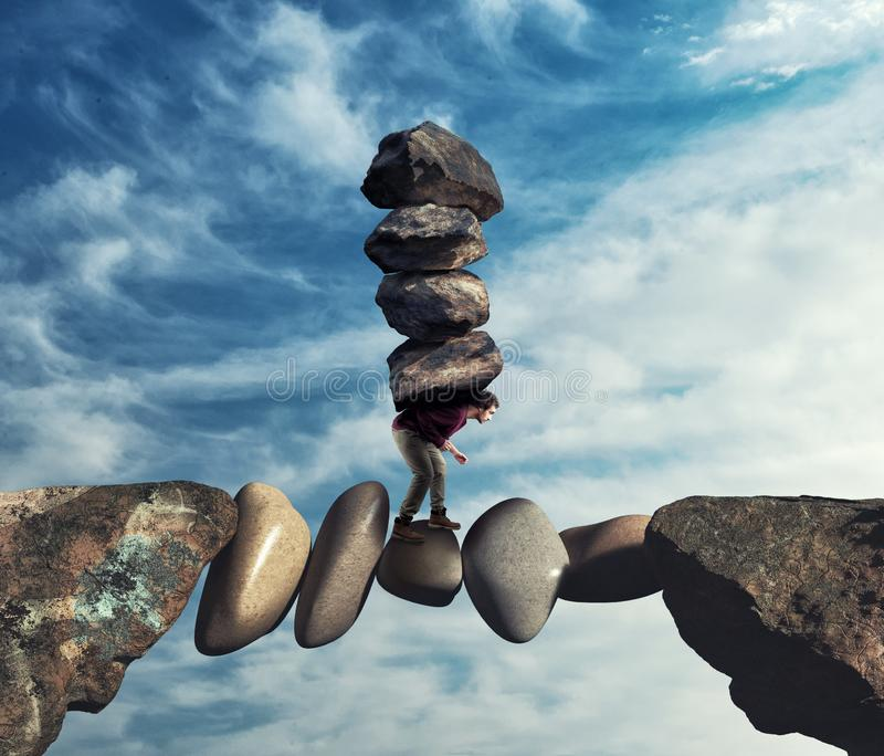 De mens draagt een stapel stenen op een onstabiele weg tussen royalty-vrije stock fotografie