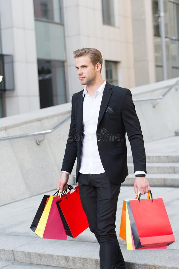 De mens draagt het winkelen zakken op stedelijke achtergrond Zakenman met pakketgang in straat Manierklant met papieren zakken stock fotografie