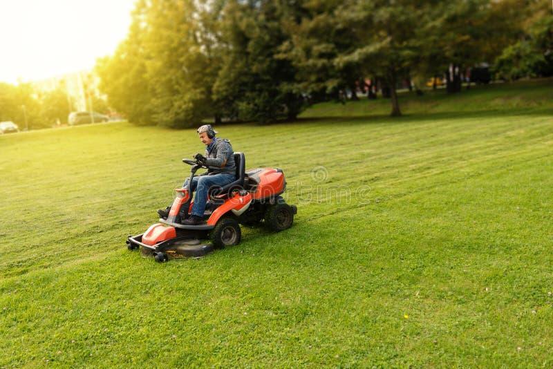 De mens drijft een grasmaaier stock afbeeldingen