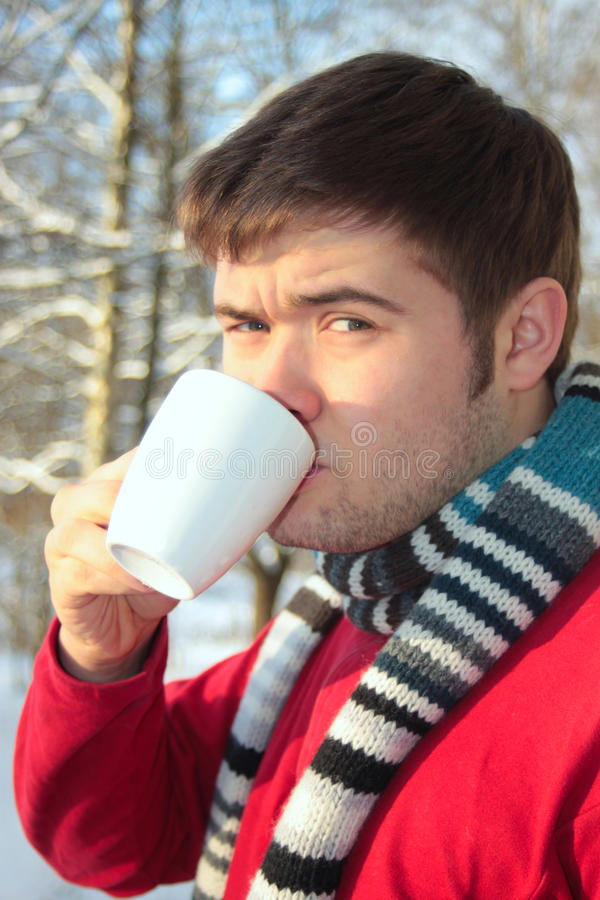 De mens drinkt hete thee in de winterbos stock fotografie