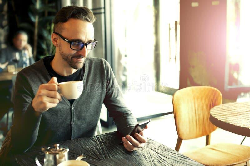 De mens drinkt koffie in een koffie royalty-vrije stock afbeelding