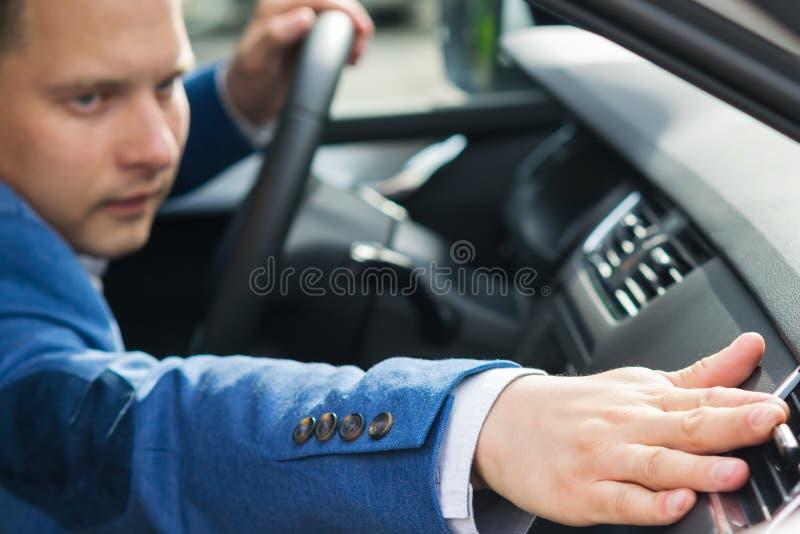 De mens in een blauw kostuum past de luchtopname in de auto aan stock fotografie