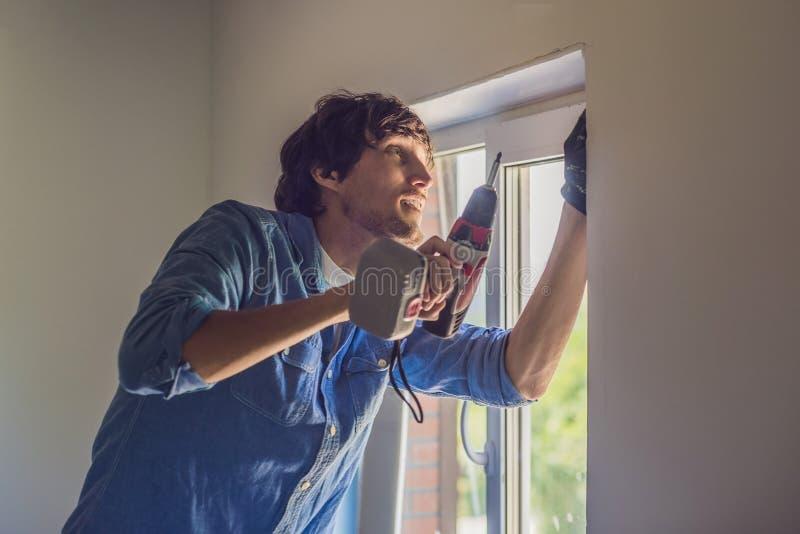 De mens in een blauw overhemd doet vensterinstallatie royalty-vrije stock afbeeldingen