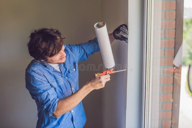 De mens in een blauw overhemd doet vensterinstallatie stock afbeeldingen