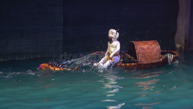 De mens in een boot en van een draakwater marionetten in Thang snakt het Theater van de Watermarionet, Hanoi, Vietnam royalty-vrije stock fotografie