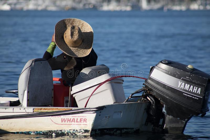 De mens in een grote strohoed zit in zijn de Walvisvaarderboot van Boston bij e royalty-vrije stock fotografie