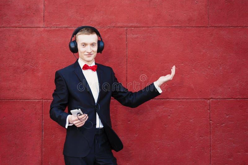 De mens in een kostuum danst De jonge kerel luistert aan muziek in grote hoofdtelefoons door smartphone Concept goede stemming en stock foto