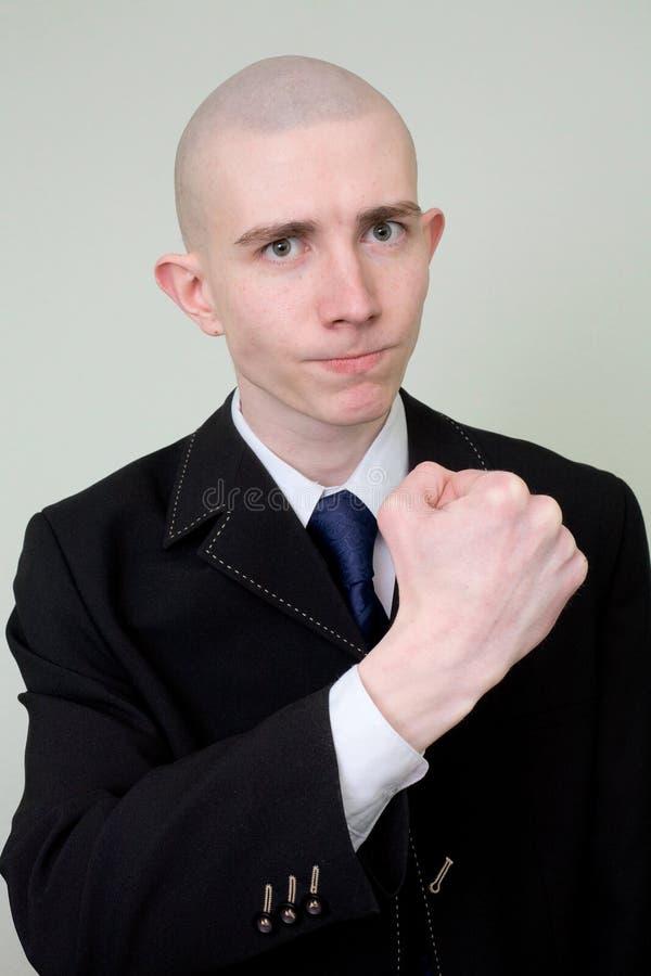 De mens in een kostuum dreigt met een vuist stock afbeelding