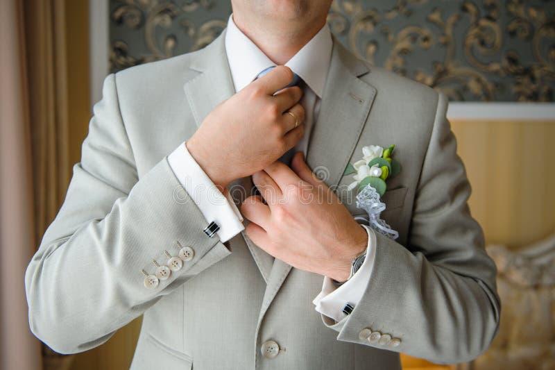 De mens in een kostuum maakt zijn band met cufflinks op hun koker recht royalty-vrije stock foto's