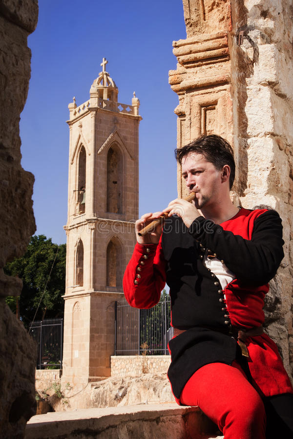 De mens in een middeleeuws kostuum speelt een fluit stock afbeelding