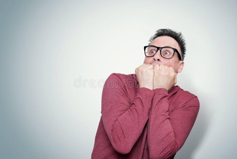 De mens in een rode T-shirt en glazen die zijn gezicht behandelen met van hem dient verschrikking in bekijkt de hemel Vreesconcep stock afbeeldingen