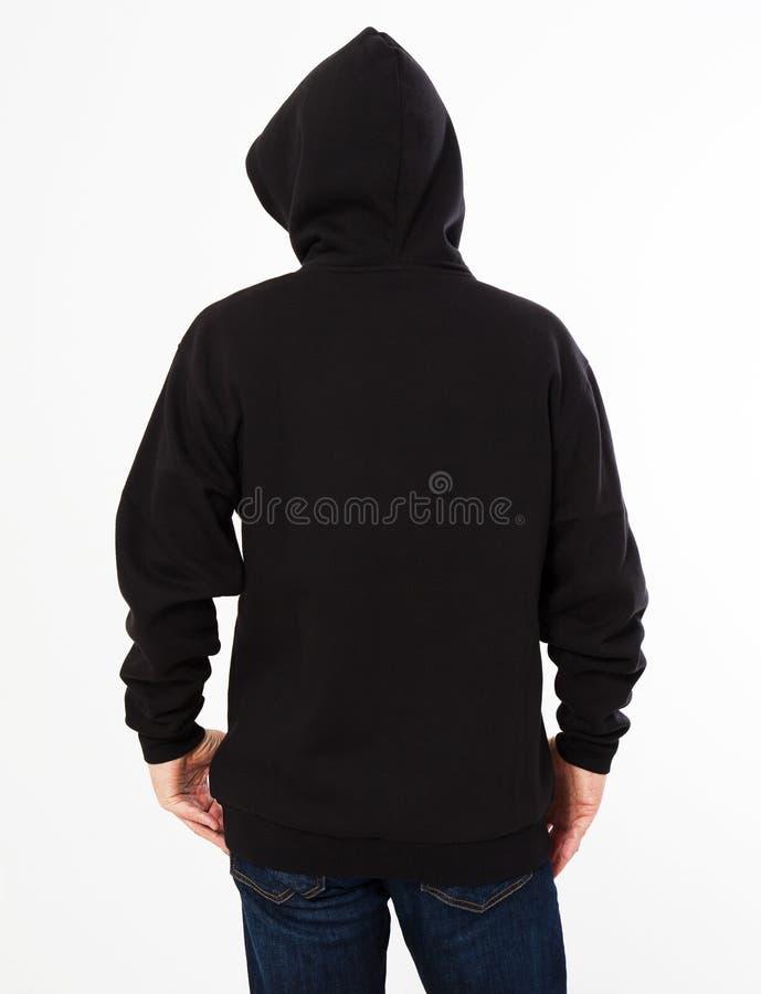 De mens in een zwart sweatshirt met een kap op zijn hoofd is geïsoleerd op een witte achtergrond - achtermening, hoogste mening royalty-vrije stock foto's