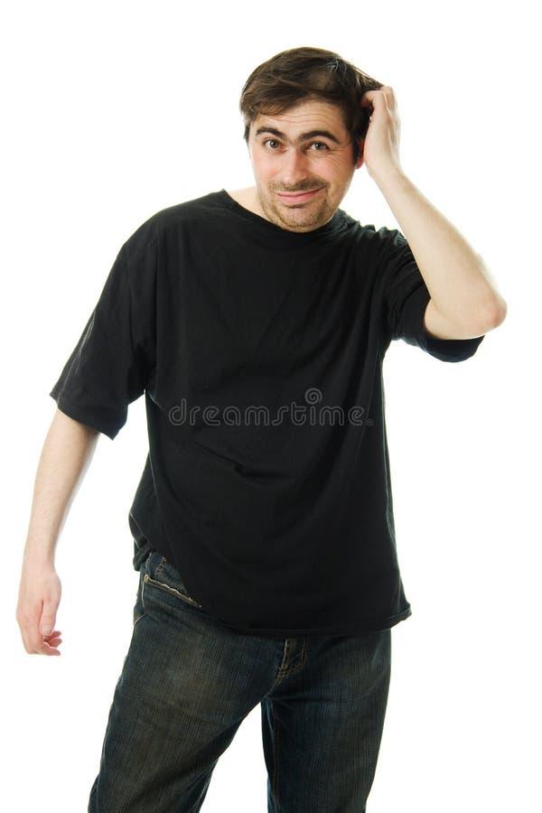 De mens in een zwarte T-shirt krast zijn hoofd. royalty-vrije stock afbeelding