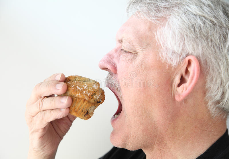 De mens eet bosbessenmuffin royalty-vrije stock afbeeldingen