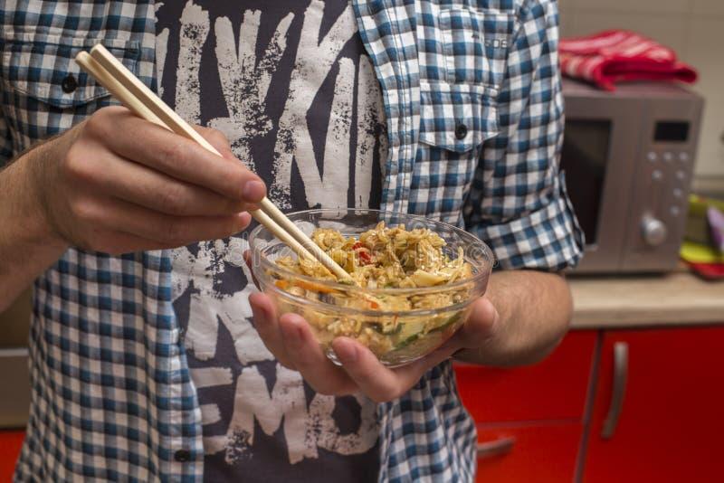 De mens eet gebraden rijst met eetstokjes voor sushi royalty-vrije stock foto