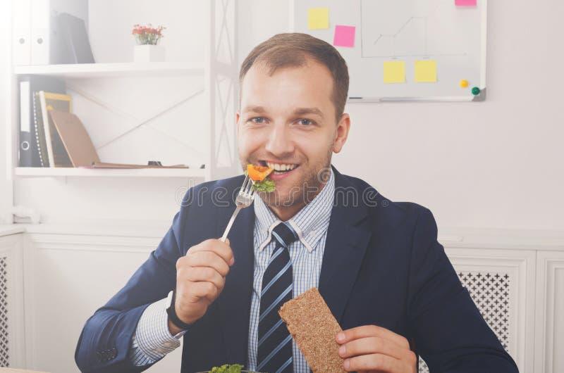 De mens eet gezonde bedrijfslunch in modern bureaubinnenland stock afbeeldingen