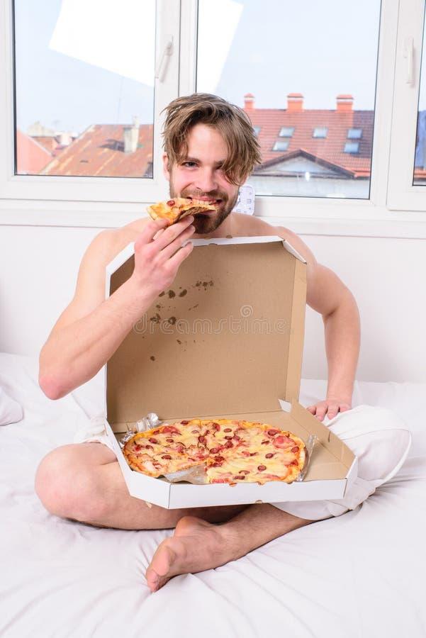 De mens eet de Kerel van het pizzaontbijt de naakte behandelde pizzadoos de aanbieding zit van de bedslaapkamer u zich bij hem aa royalty-vrije stock foto
