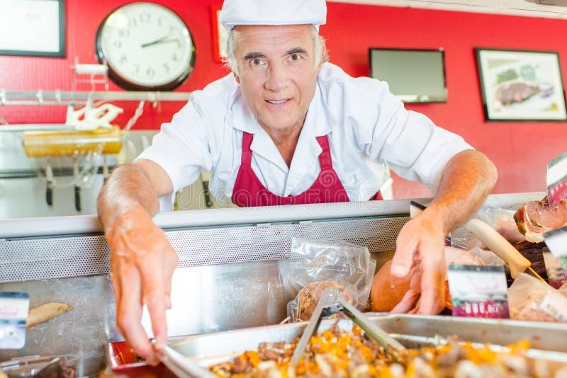 De mens en bereidt voedsel op het werk van te voren stock afbeelding