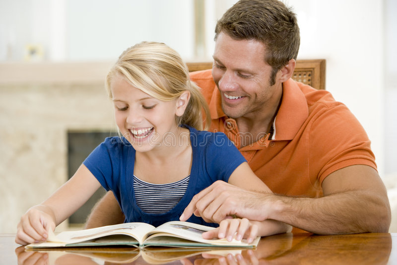 De mens en de jonge meisjeslezing boeken in eetkamer royalty-vrije stock foto