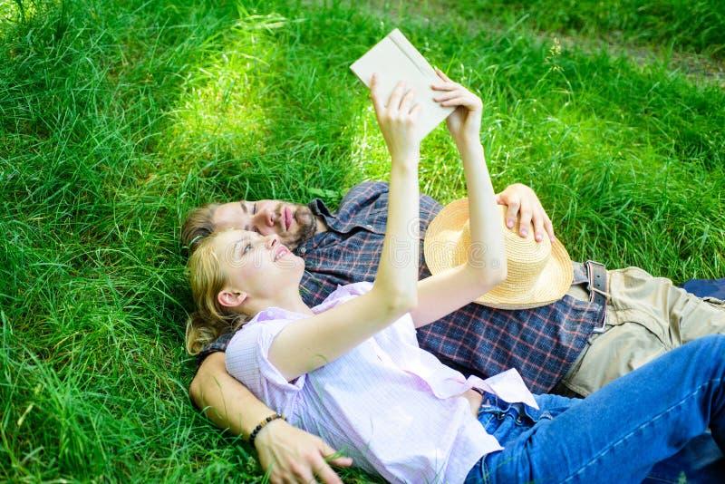 De mens en het meisje leggen op gras die pret hebben Het paar in liefde besteedt het boek van de vrije tijdslezing De romantische stock foto