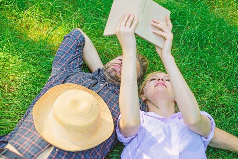 De mens en het meisje leggen op gras die pret hebben Het paar in liefde besteedt het boek van de vrije tijdslezing Paar soulmates stock afbeeldingen