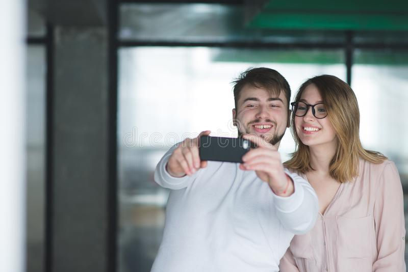 de mens en het meisje maken binnen selfie Mooi paar beambten om selfie smartphone te maken royalty-vrije stock foto's