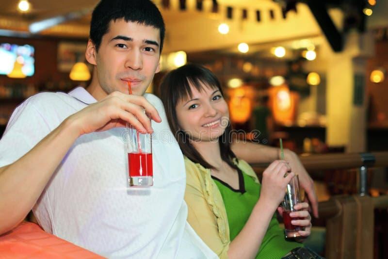 De mens en het meisje zitten en drinken cocktail stock afbeeldingen