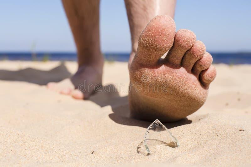 De mens gaat op het strand en het risico om op een splinter van gebroken flessenglas te stappen stock foto's