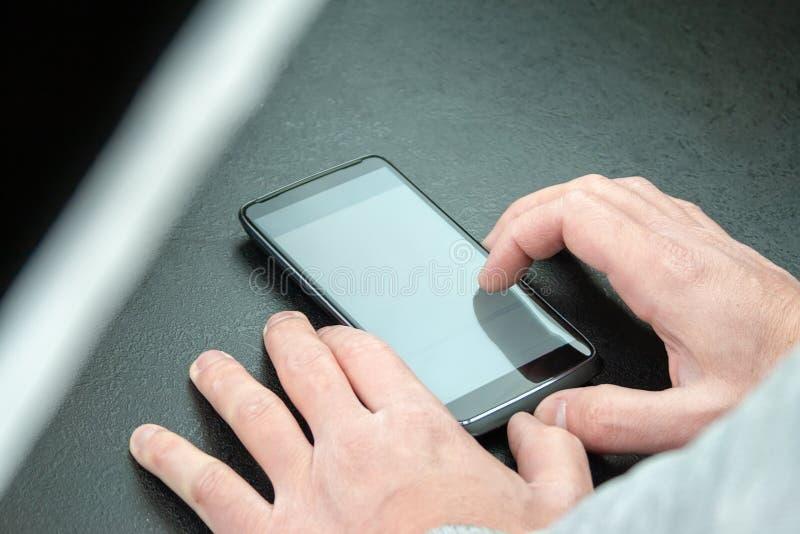 De mens gebruikt een mobiele telefoon op de lijst royalty-vrije stock foto