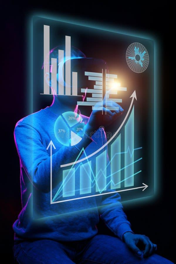 De mens gebruikt een virtuele werkelijkheidshoofdtelefoon om met gegevens in de vorm van grafieken en grafieken te werken stock afbeeldingen