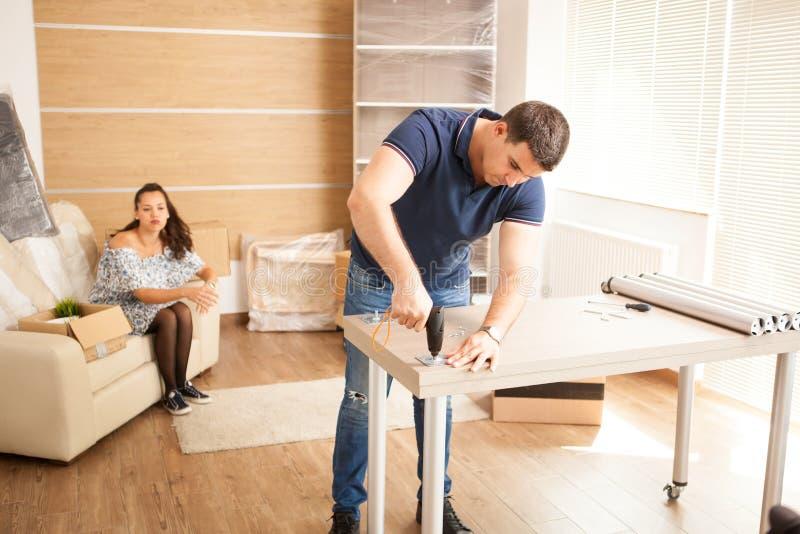 De mens gebruikt hulpmiddelen aan assemblagemeubilair in nieuw huis stock afbeeldingen