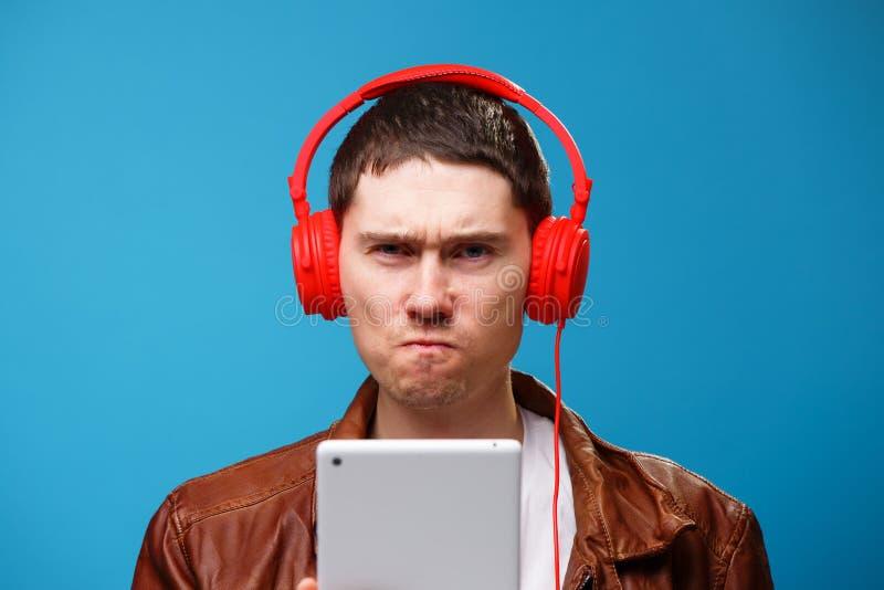 De mens gebruikt tabletcomputer en luistert aan muziek met hoofdtelefoons royalty-vrije stock fotografie