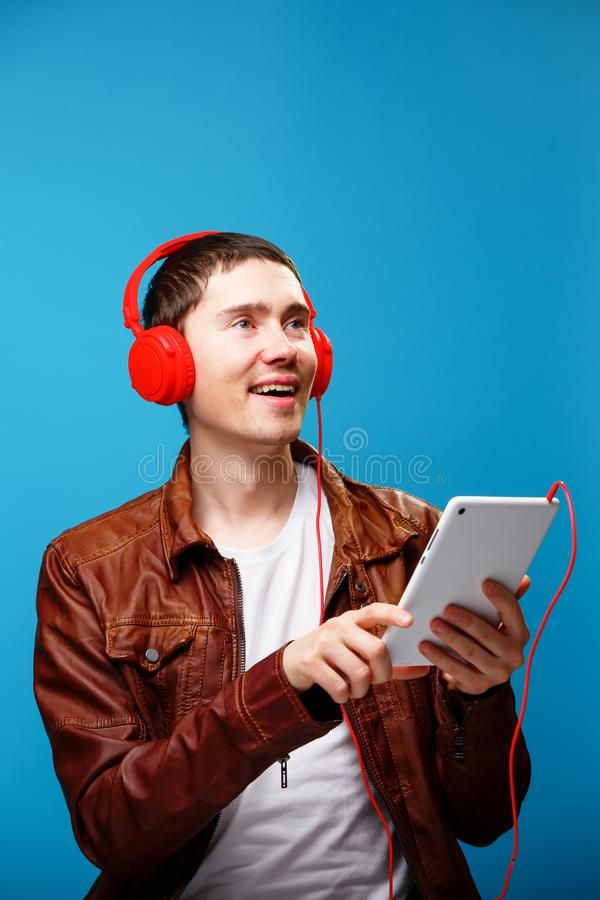 De mens gebruikt tabletcomputer en luistert aan muziek met hoofdtelefoons stock fotografie