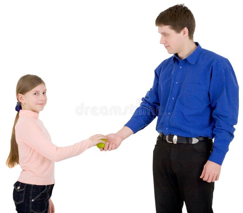 De mens geeft appel aan het meisje royalty-vrije stock afbeeldingen