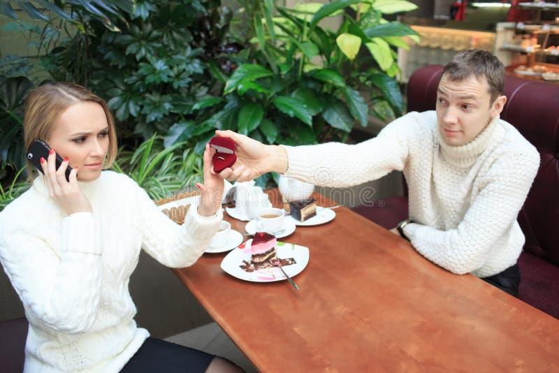 De mens geeft het meisje een ring Vrouw die op telefoon spreekt royalty-vrije stock foto's