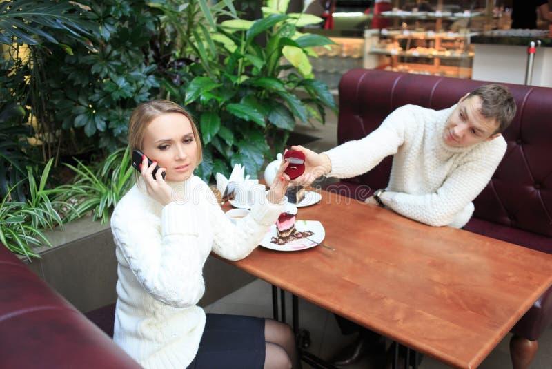 De mens geeft het meisje een ring Vrouw die op telefoon spreekt stock afbeeldingen