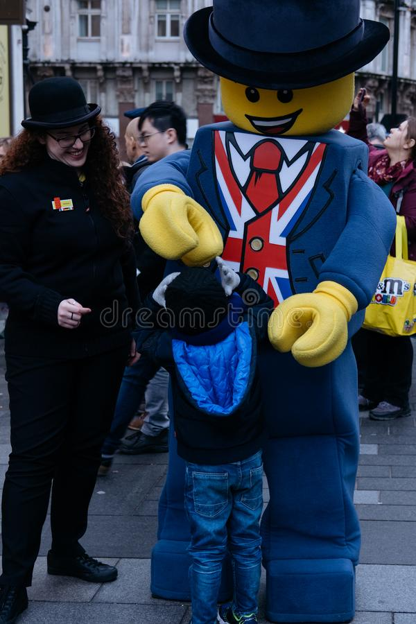De mens gekleed in een Lego Man-kostuum en een winkeldeelnemer gaan met een jongen voor de LEGO-opslag in Leicester, Londen, het  stock afbeeldingen