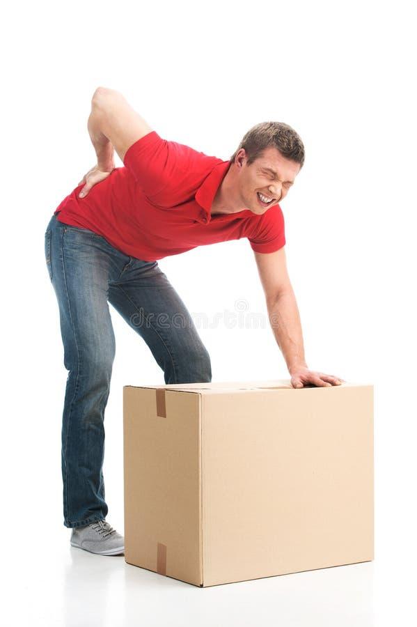 De mens gekleed in toevallige kleding kwetste zijn rug die grote doos opheffen stock foto