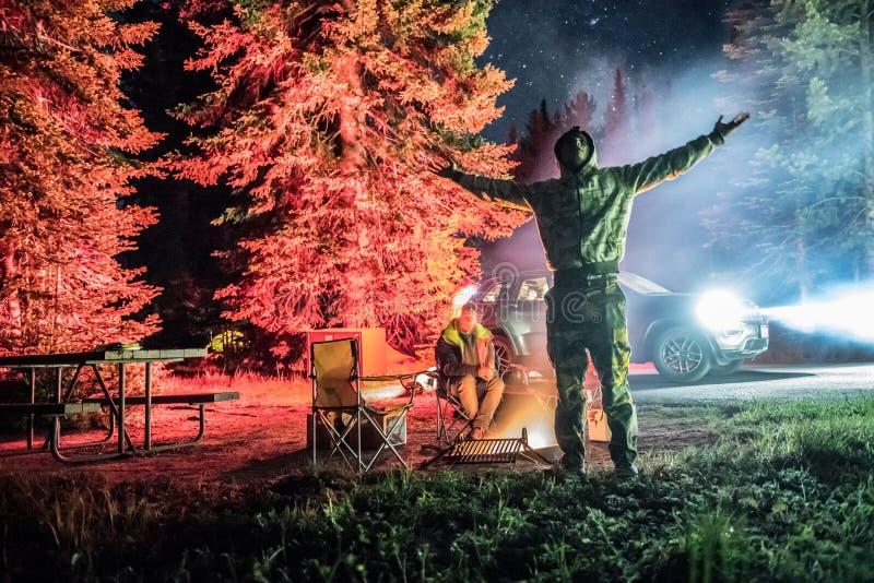 De mens geniet aard van vrijheid op vakantie op een kampeerterrein en onderzoekt de nachthemel met opgeheven handen stock foto's