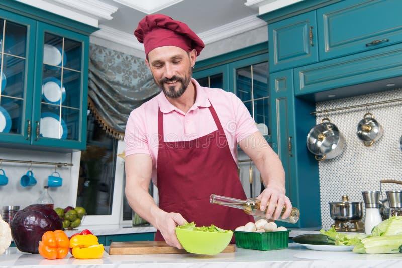 De mens giet olijfolie in kom met plantaardige salade Voorbereiding van smakelijk en gezond voedsel thuis Het koken en huisconcep stock foto