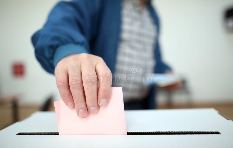 De mens giet zijn stemming bij verkiezingen stock foto