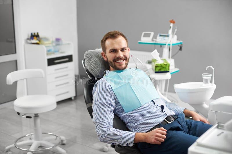 De mens glimlacht aan de camera terwijl het zitten als tandvoorzitter in tandheelkunde die gelukkig en tevreden met zijn behandel stock foto