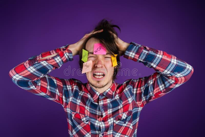 De mens grijpt zijn hoofd, schreeuwt met zijn gesloten ogen en zijn open mond, stickers op zijn gezicht Een mens wordt geschokt d royalty-vrije stock foto's