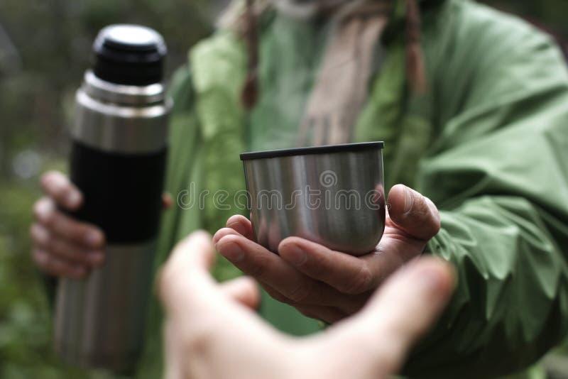 De mens in groen jasje biedt een hete drank - thee of koffie van thermosflessen aan iemand aan wie een hand, eerste persoonsmenin royalty-vrije stock fotografie